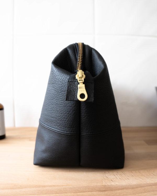 Seitenanischt der Bügeltasche aus schwarzem Kunstleder. Hochwertig verarbeitet.